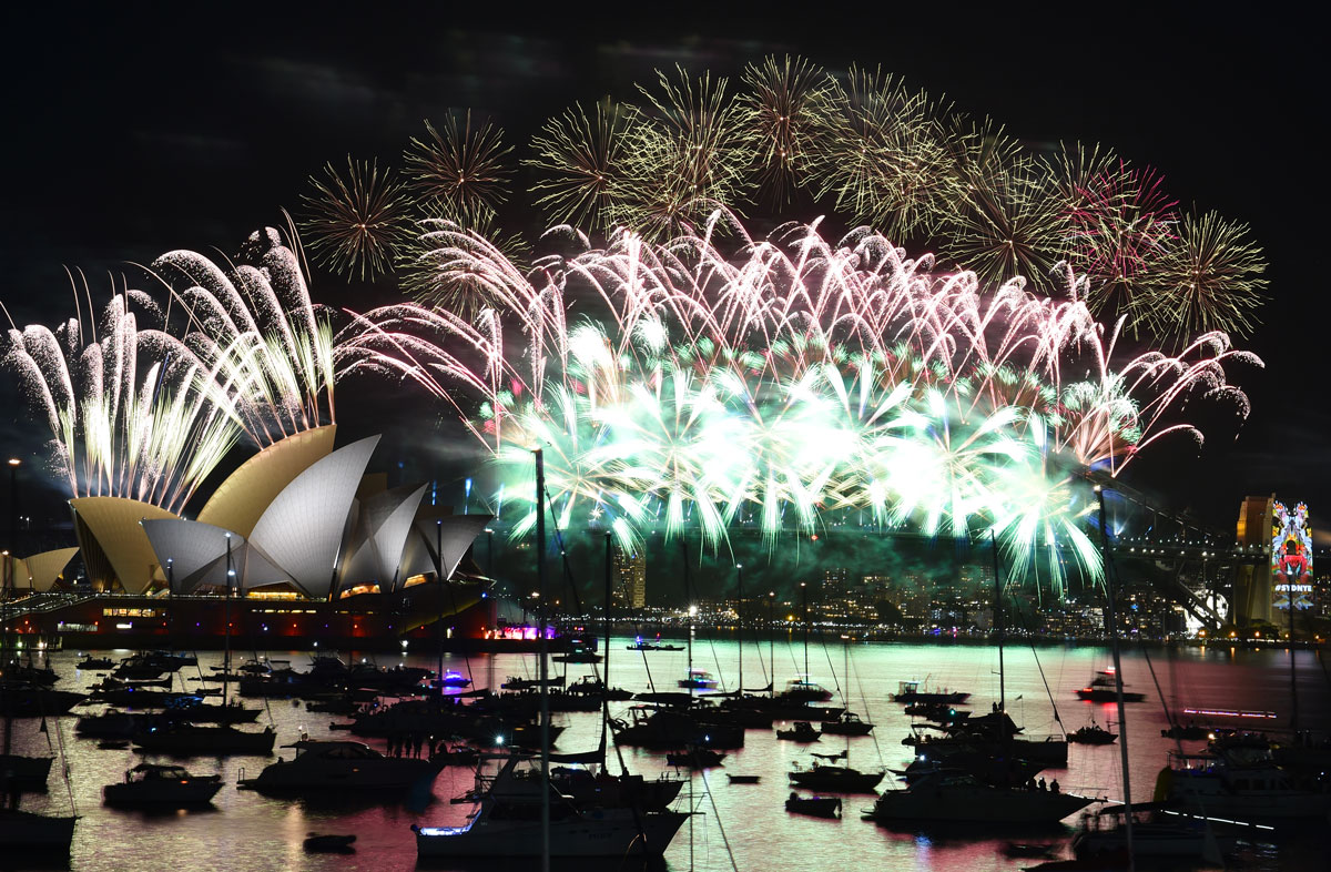 Fireworks light up the sky over Sydney's Opera House (L) and Harbour Bridge during New Year celebrations in Sydney on January 1, 2016. AFP PHOTO / Saeed KHAN / AFP / SAEED KHAN